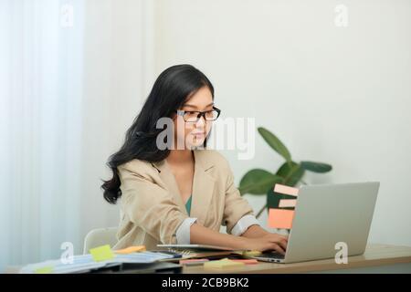 Head shot agradable mujer joven feliz trabajando en la computadora en casa.