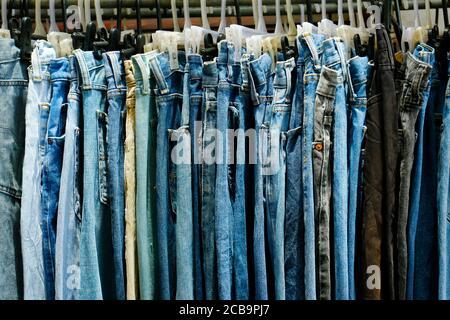 surtido de pantalones vaqueros azules colgados en una tienda Foto de stock
