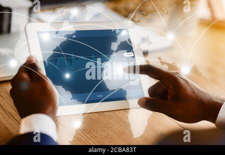 Hombre de negocios negro tocando la pantalla de la tableta digital con el holograma de mapa de negocios