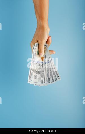 Wad de billetes en mano sobre fondo azul. El concepto de asistencia financiera. Foto de stock