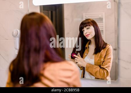 Vista posterior de la hermosa mujer joven en camiseta blanca y camisa de yello, peinando su pelo rojo oscuro recto y sonriendo mientras mira en el espejo