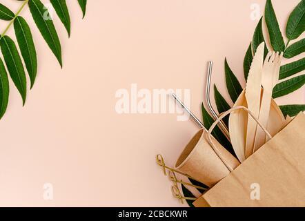 Juego libre de plástico con bambú, cubiertos de papel y pajitas de metal sobre fondo rosa. Concepto de cero residuos.