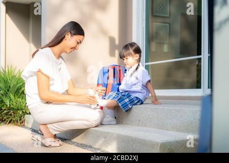 Madre asiática ayudando a su hija a ponerse zapatos o despegar en el parque al aire libre preparándose para salir juntos o volver a casa de la escuela en feliz f
