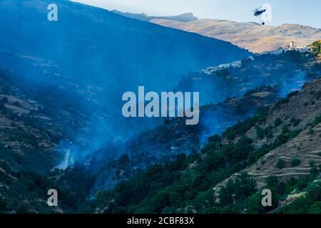 Helicóptero con bolsa de agua trabajando para extinguir un incendio en las Alpujarras de Granada.