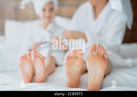 mujer de cerca y niño piernas acostadas en la cama blanca usando albornoz y toalla