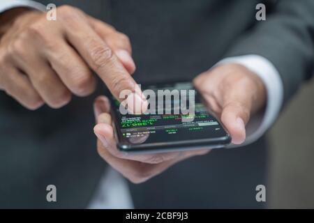 Primer plano de las manos humanas que comprueban las cartas de acciones financieras en.