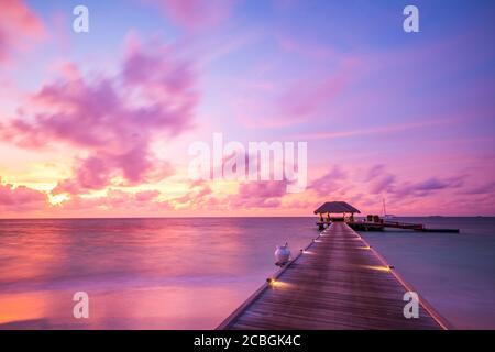 Isla Maldivas puesta de sol. Complejo de bungalows acuáticos en la playa de las islas. Océano Índico, Maldivas. Hermoso paisaje al atardecer, complejo de lujo y cielo colorido.