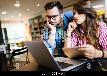 Concepto de universidad, estudio, universidad y educación. Grupo de estudiantes cansados aprendiendo en la biblioteca