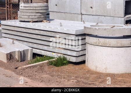 Losas de hormigón armado y anillos para el sistema de alcantarillado en el sitio de construcción. Producción industrial de productos de cemento.