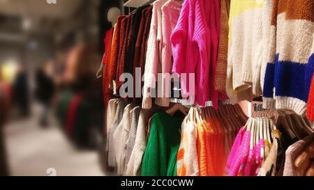 Suéteres en una percha en una tienda - fondo borroso para texto