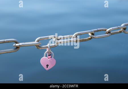 Amor candados en rosa colgando en la valla de la cadena de metal