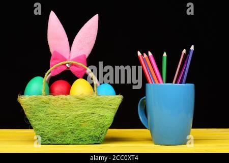 Niñas orejas de conejito de Pascua en color rosa de pie en cesta de tela verde llena de huevos pintados y colores crayones en taza azul colocado cerca en mesa de madera amarilla, sobre fondo negro.
