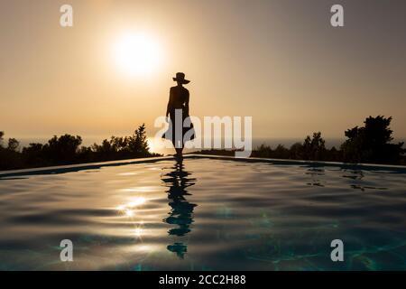 Silueta de una chica de pie en el borde de una piscina infinita viendo la puesta de sol sobre el mar, Lefkada, Islas Jónicas, Grecia Foto de stock