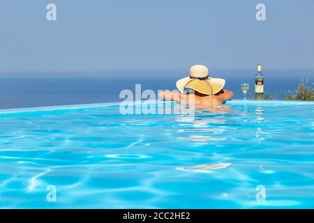Una chica en un sombrero de sol con una botella de vino apoyada en el borde de una piscina infinita y mirando hacia el mar, Lefkada, Islas Jónicas, Grecia Foto de stock