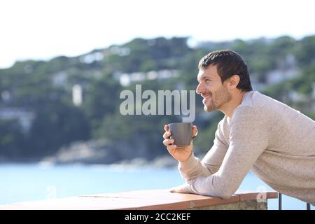 Vista lateral de un hombre feliz contemplando vistas con café copa en un balcón en la playa