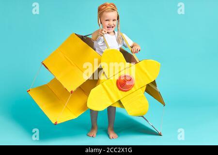 Niño juguetón con camiseta blanca y avión de juguete, casco en la cabecera felizmente lokking en camer en aislado estudio azul. Cielo, piloto, aviación conceps