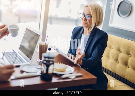 mujer de negocios de éxito compartiendo con sus secretos de negocio. de cerca vista lateral foto. mujer de edad encantadora hablando con un cliente en el café