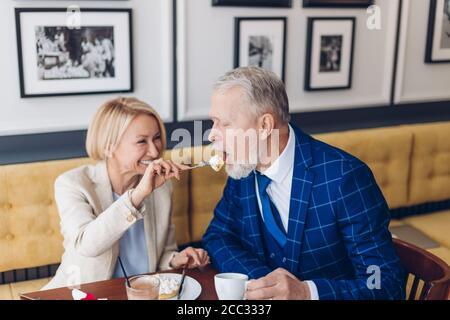 pareja de la familia feliz comiendo pastel en el café juntos. foto de cerca. mujer hermosa positiva tratando a su marido con postre delicioso