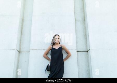 Retrato al aire libre de la bonita chica de moda posando en la pared blanca de la ciudad.