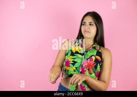 Joven hermosa mujer de pie sobre fondo rosado aislado expresión disgustada, disgustado y temeroso haciendo cara de disgusto porque la reacción de aversión