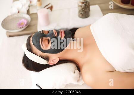 Concepto Spa. Mujer joven con máscara facial de nutrientes en un salón de belleza, cerrar