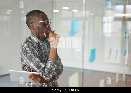 Un hombre de negocios africano pensivo con gafas de pie frente al vidrio la pared y mirando las notas adhesivas en ella él él piensa sobre nuevas ideas