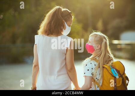 La vida durante la pandemia de covid-19. Vista desde detrás de la madre y el niño con máscaras, mochila amarilla y antiséptico que vuelve de la escuela fuera.