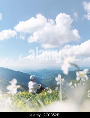Un turista con ropa blanca se sienta en una pradera de montaña cubierta de flores blancas narciso. Montañas Cárpatos, Europa. Fotografía de paisajes