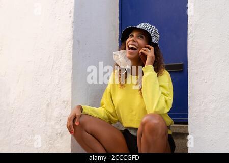 Retrato de una atractiva mujer negra sentada y hablando con el teléfono móvil al aire libre con su máscara apagada. Concepto de comunicación