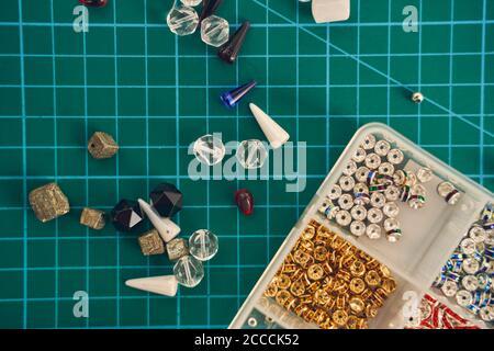 Cuentas de vidrio y semillas o de fieltro para la fabricación de joyas fondo verde