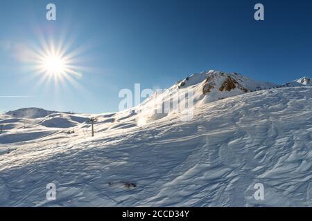 Vista panorámica de la montaña alpina cubierta de nieve en el soleado día de invierno. Picos nevados con el sol brillante y vibrante sobre el cielo azul claro. Panorámica