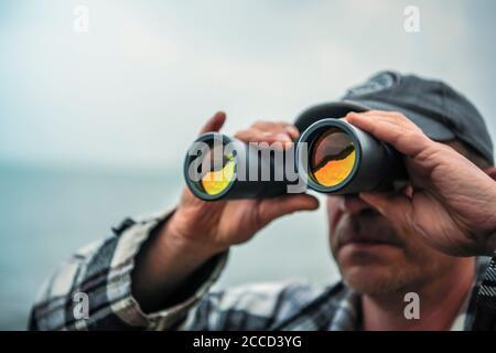 Primer plano de hombre mirando a través de prismáticos con cara no visible.