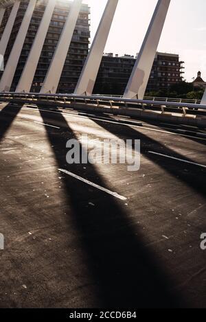 Sol y sombra en el camino de un puente de metal urbano, imagen vertical para portadas de libros.