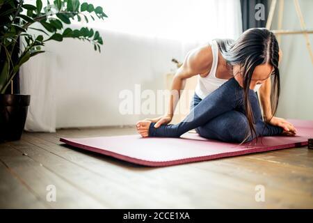joven y esbelta mujer caucásica estirándose en casa, mujer en ropa deportiva haciendo ejercicios en casa durante la cuarentena