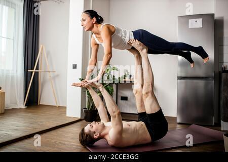 joven matrimonio caucásico realizando una postura de acro yoga en casa, hombre apoyando a la mujer en sus piernas y brazos, estirando y haciendo ejercicios tog Foto de stock