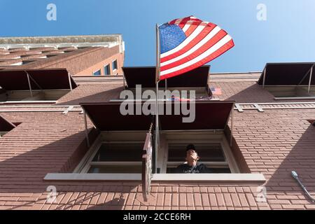 Tulsa, OK, EE.UU. 20 de junio de 2020. Un hombre observa a una multitud de partidarios y manifestantes de Trump cerca de una entrada al mitin del presidente Donald Trump cerca del centro de BOK. Foto de stock