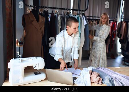 Jóvenes diseñadores de ropa trabajan en el ordenador portátil en el estudio. Fondo hermosa señora de pie cerca de un estante de ropa. Uso del portátil en el lugar de trabajo