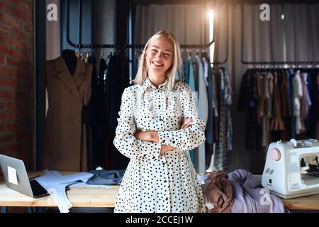 Hermoso puesto de diseñador de moda caucásico y felizmente sonrisa en el lugar de trabajo, mirar la cámara. Vestido con vestido blanco. Estudio de diseño de fondo