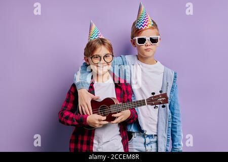 retrato de niños hermosos en feliz cumpleaños con sombrero de vacaciones en la cabeza y sosteniendo uculele, tocando música. amistad, niños, cumpleaños con Foto de stock