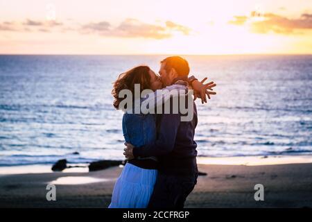 Pareja romántica disfrutando de la puesta de sol en la playa besando y amando el uno al otro - la gente caucásica tiene vacaciones románticas de verano vacaciones abrazando togeth