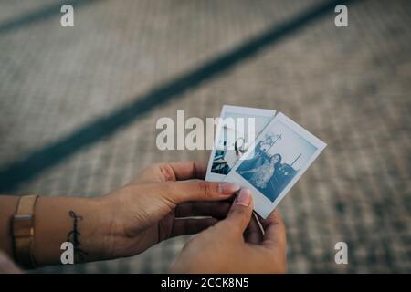 Primer plano de las manos de la mujer sosteniendo fotografías al aire libre