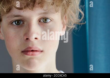 primer plano retrato de un adolescente con cabeza roja y un aspecto desconcertante, un niño caucásico con ojos verdes mira con confianza a la cámara