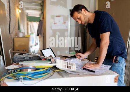 Hombre trabajando en el plan de construcción y la muestra de color