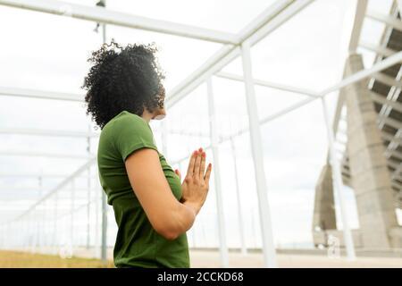 Mujer adulta mediana meditando mientras está de pie contra la estructura construida ciudad Foto de stock