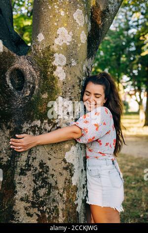 Sonriente joven con los ojos cerrados abrazando el tronco del árbol mientras de pie en el parque