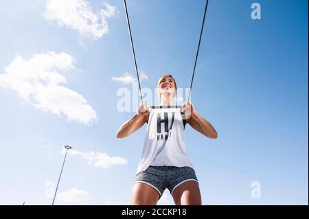 Sonriendo mujer adulta media haciendo ejercicio con correa contra el cielo durante día soleado Foto de stock