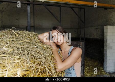 Mujer joven con los ojos cerrados apoyándose en la paja en un granero en una granja