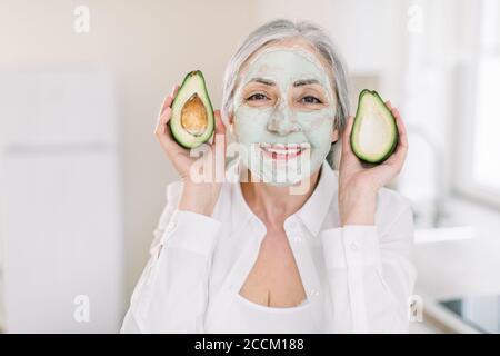 Concepto de belleza, antiarrugas y cuidado de la piel. Primer plano de la feliz mujer de pelo de alta calidad con camisa blanca, con máscara facial de barro, mostrando