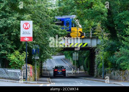 Tren de pasajeros del ferrocarril del norte, pasando la señal de la estación en el puente de ferrocarril bajo y coche en la carretera rural del pueblo - Burley, Yorkshire, Inglaterra, Reino Unido Foto de stock