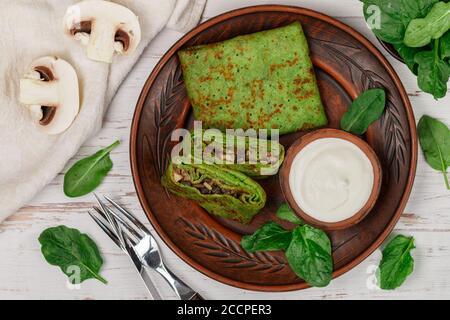 Panqueques verdes de espinaca (crepes) rellenos de setas con crema agria. Delicioso desayuno saludable en un plato de arcilla en un backgroun de madera clara